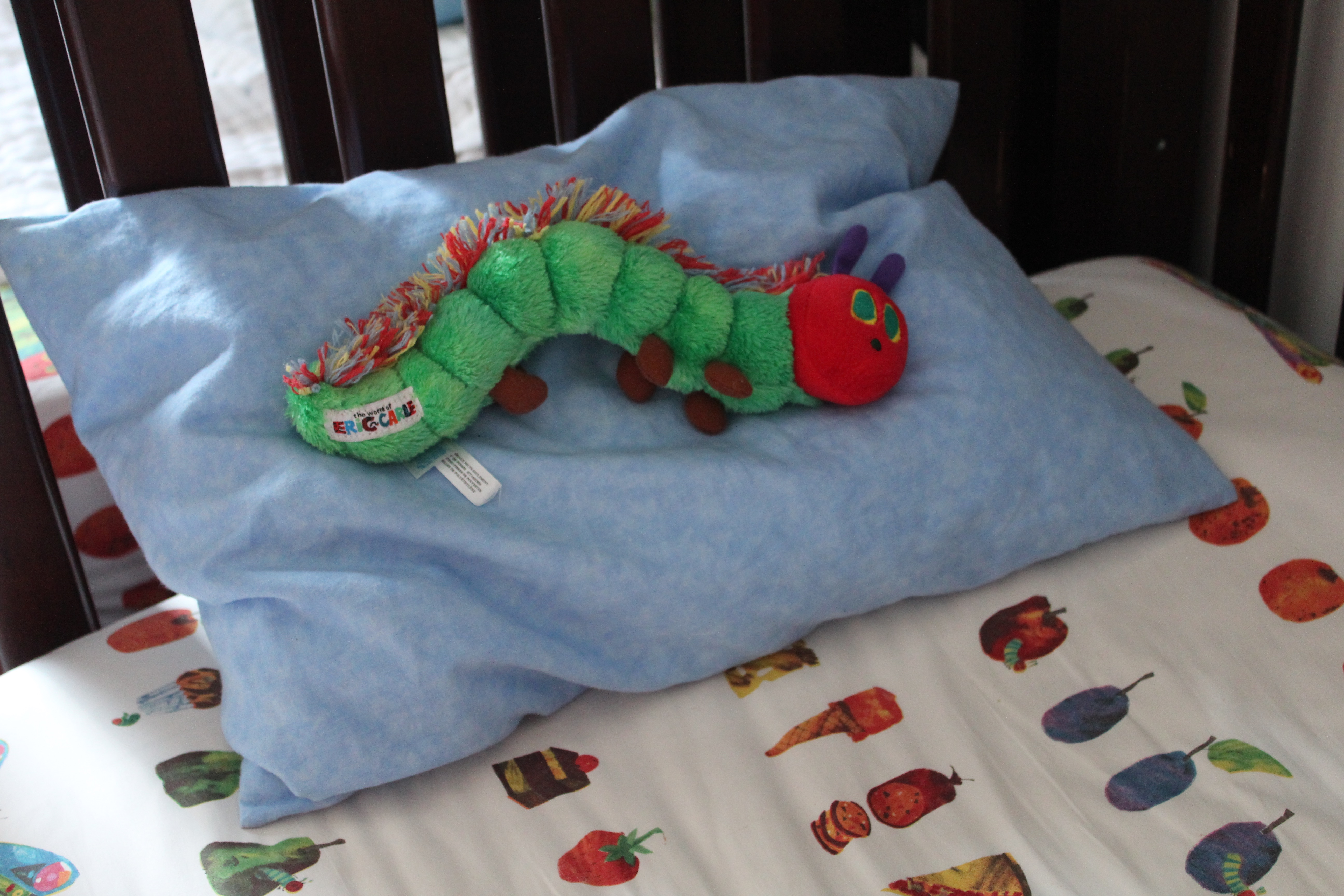 Very Hungry Caterpillar doll on Very Hungry Caterpillar bedspread.