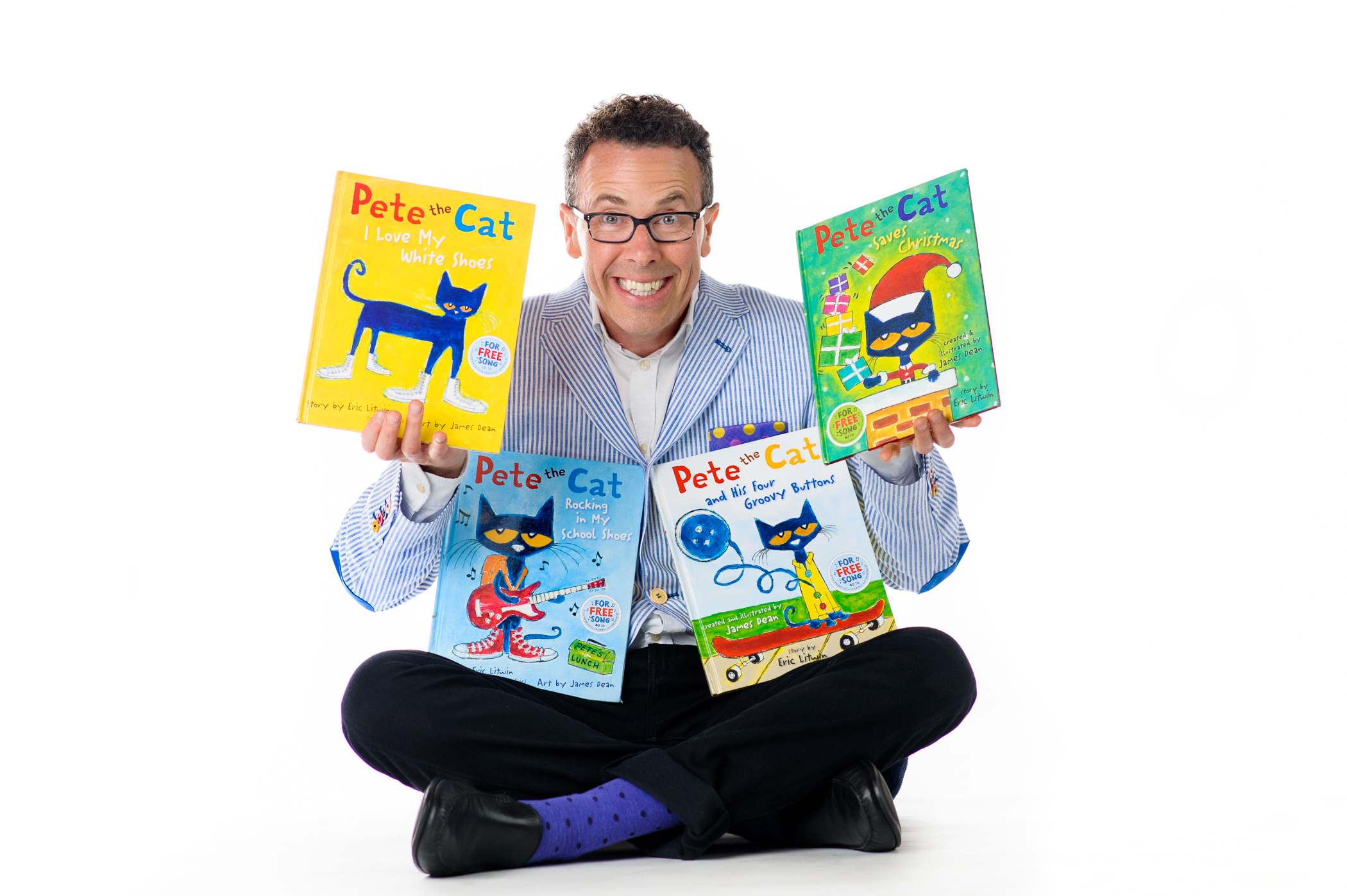 photo of Eric Litwin holding the four Pete the Cat books he authored